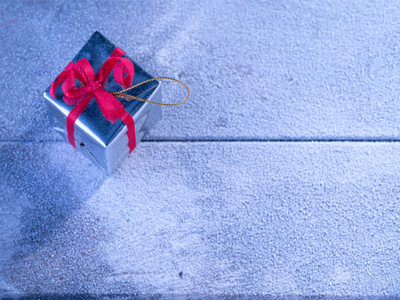 snowbound: close up view  of  gift box on snowbound  wooden back Stock Photo