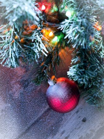 snowbound: close up view  of lit Christmas tree on snowbound  wooden back