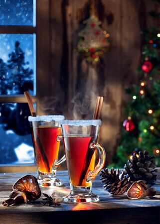 newyear: close up view  of glass with mulled wine with gift boxes on color back