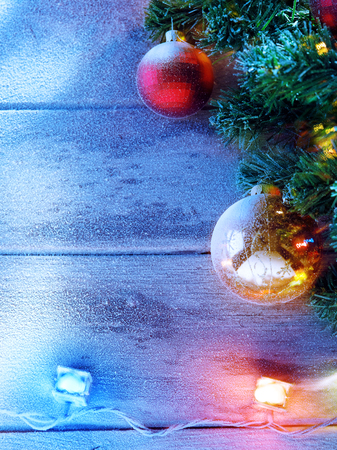 newyear: close up view  of lit Christmas tree on snowbound  wooden back