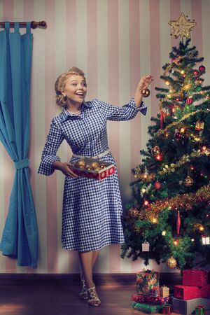 portrait of nice young woman hanging around christmas tree on x-mas  eve Stock Photo