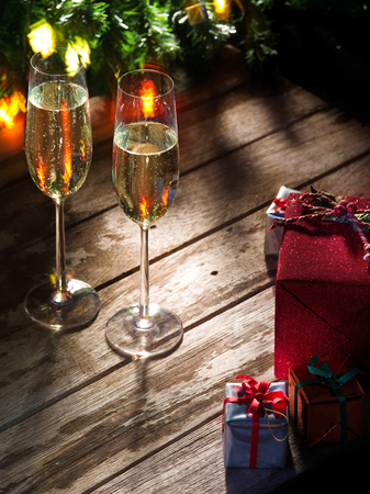 happy christmas: view of two glasses  of champagne with gift boxes on color back Stock Photo