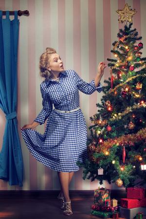 newyear: portrait of nice young woman hanging around christmas tree on x-mas  eve Stock Photo