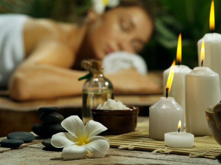 portrait of young beautiful woman in spa environment.  focused on candles Stockfoto