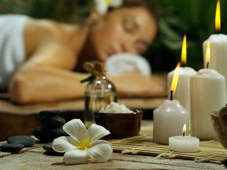 Retrato de mujer joven y bella en el entorno de spa. centrado en las velas Foto de archivo - 73005118