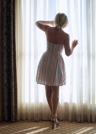 portrait of young  beautiful woman looking in the window