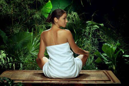 Mening van het aardige jonge vrouw mediteren in kuuroord tropisch milieu Stockfoto