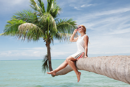 hummock: view of nice young lady sitting on palm trunk on tropical beach