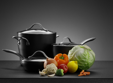 stewing: close up view of nice cookware set with some vegetables on grey back