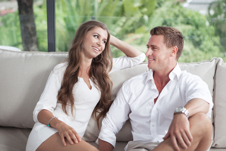 View of nice young couple is sitting on sofa in summer house Stock Photo