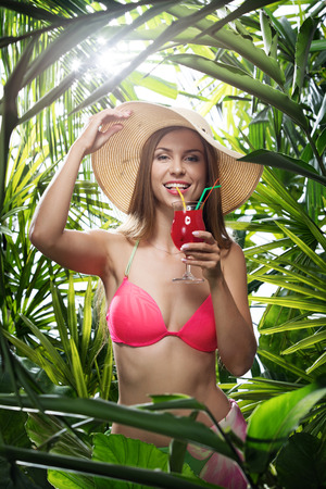 portrait of nice young woman is hanging in tropical jungle