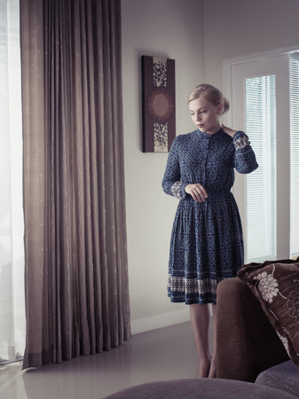 Portrait of young woman in color dress staying thoughtful in room