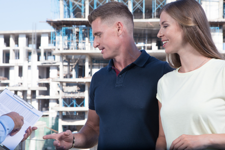 portrait of nice young couple studying contract on construction area background
