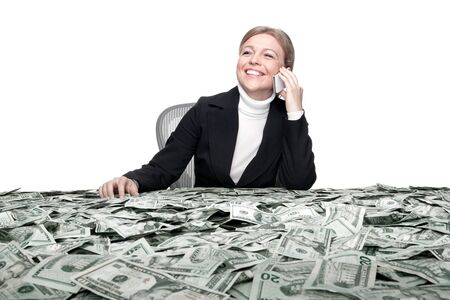 portrait of young woman sitting behind the table full of cash Stock Photo