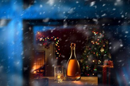 close up view  of glass with cognac and bottle  in Christmas environment Фото со стока - 131493364