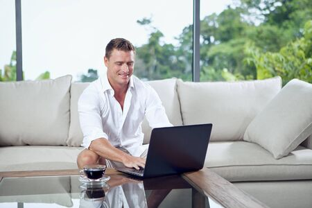 portrait of young man sitting on sofa with laptop in summer house environment