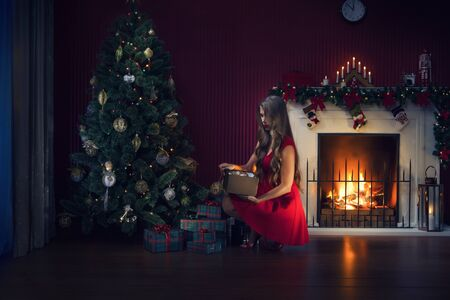 portrait of nice woman in red dress with gifts  in christmas environment Фото со стока