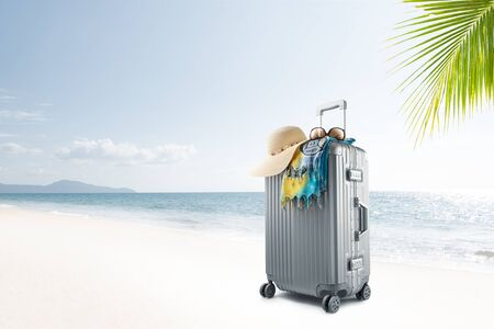 View of gray suitcase with pareo and hat on tropical beach Banque d'images
