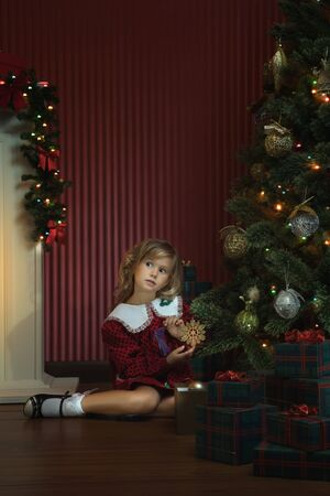 portrait of little girl is waiting for Santa coming in domestic environment