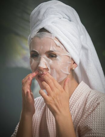 close up portrait of nice young woman applying facial mask