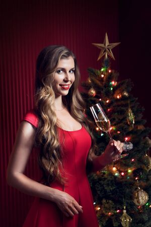 portrait of nice woman in red dress with champagne  in christmas environment