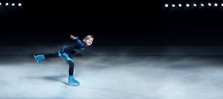 view of child  figure skater on dark ice arena background