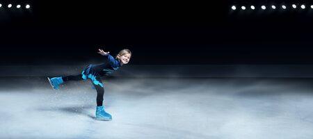 Vista de la patinadora artística infantil sobre fondo de arena de hielo oscuro