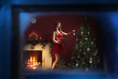 portrait of nice woman in red dress decorating christmas tree
