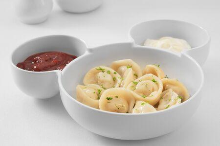 vista ravvicinata del piatto con gnocchi su sfondo bianco.