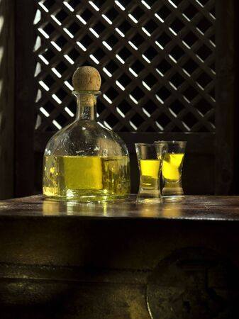 Close up view of bottle of tequila anejo and glasses on color background