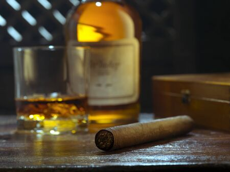 NO LOGOS OR TRADEMARKS! SELF MADE LABELS! close up view of cigar, bottle of whiskey and a glass aside on color back.
