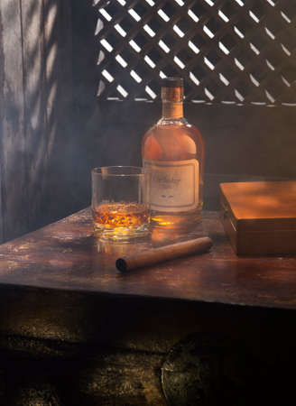 close up view of cigar, bottle of whiskey and a glass aside on color back.