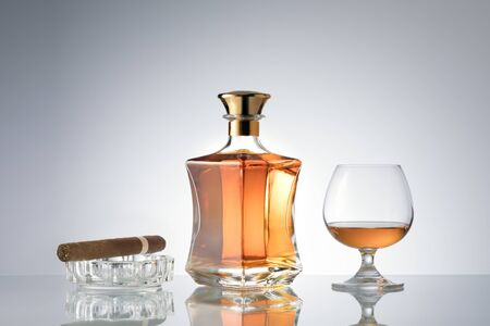 close up view of cigar, bottle of cognac and a glass aside on grey back.