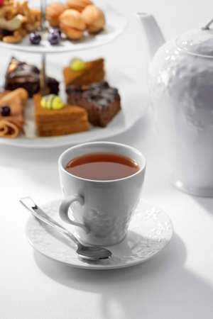 Close up view of dessert plate, china teapot and cups on white background Standard-Bild