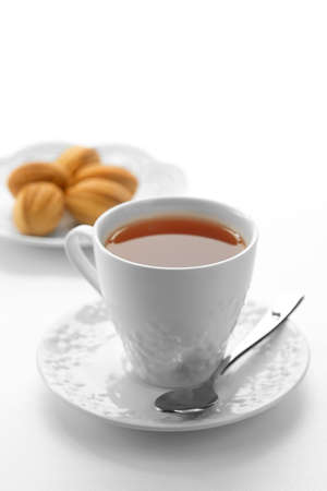 Close up view of dessert plate and cup of tea on white background