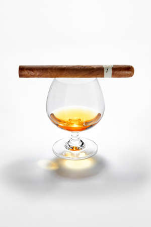 NO LOGOS OR TRADEMARKS!  SELF MADE LABELS! Close up view of glass of whiskey with cigar on top on white back Reklamní fotografie