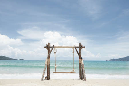View of nice wooden swing on summer tropic beach