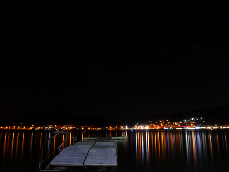 Night photo of pier. bright night lights reflection on the sea water. Stock Photo