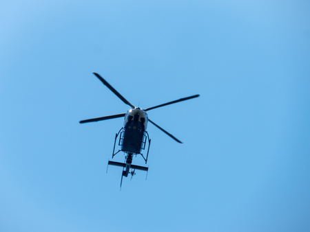 Flying helicopters in the blue open sky.