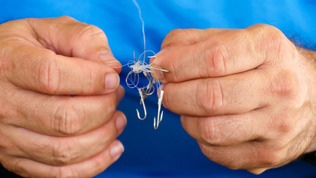 Man unraveling to the tangled and knotted Fishing line. Problem solving.