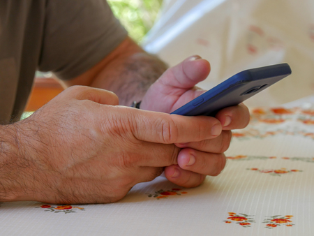 Closeup image of a man holding , using and looking at smart phone