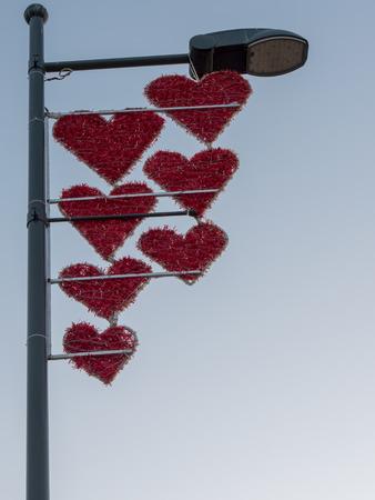 Red heart shape over blue sky background. love sign red hearts on light pole. Stok Fotoğraf