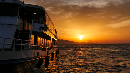 Side view of ferry boat at sunset. Aegean or Mediterranean sea background.