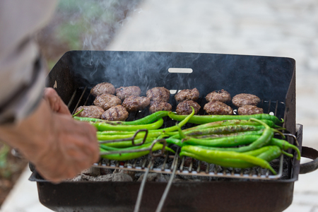 Meatballs and long green peppers on the Grill