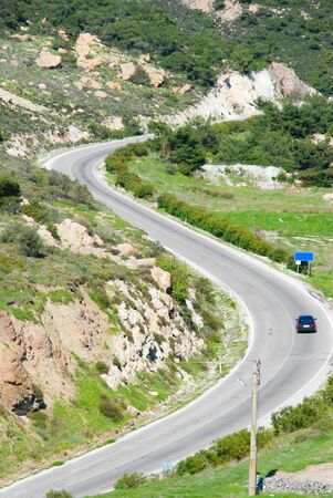 Road with car leading through the mountain landscape in S curved road. background.