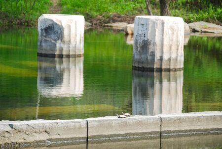 Ancient columns with water reflection at archeological site area.
