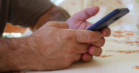 Man using his smartphone with to scrolling, tapping on screen. Close-up. Stock Photo