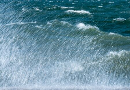 Waves hit the hard surface of concrete wall and splashing sea water.
