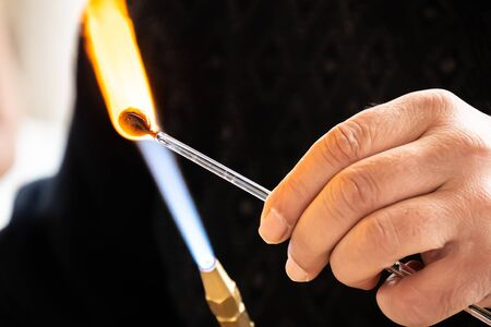 Hands of the handicrafts man making a glass subject of crafts. Glass maker working melted glass with a flaming torch. Close up of flame from blowtorch on new glass art piece. Banco de Imagens