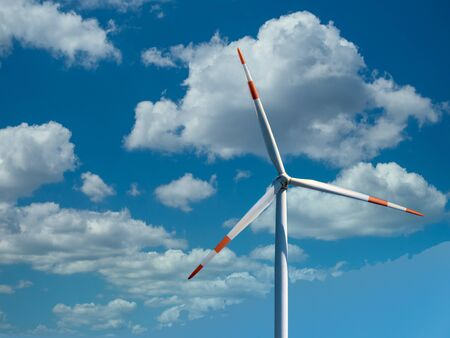 Wind turbine with beautiful clouds on the sky background. Renewable alternative energy.